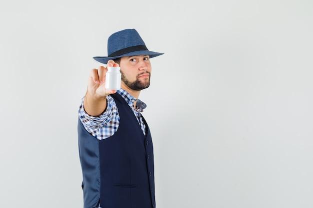 Молодой человек показывает бутылку таблеток в рубашке, жилете, шляпе и выглядит уверенно