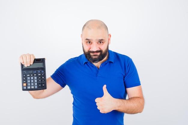 電卓を見せて、青いシャツを着て親指を上げて、満足そうに見える若い男。正面図。