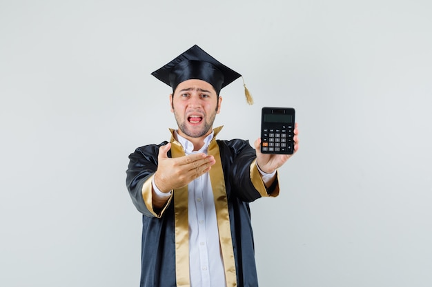 卒業式の制服を着て電卓を見せて困惑している若い男、正面図。