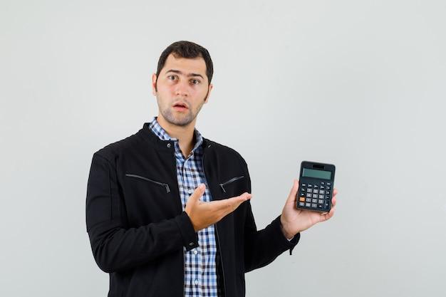Молодой человек показывает калькулятор в рубашке, куртке и смотрит озадаченно, вид спереди.