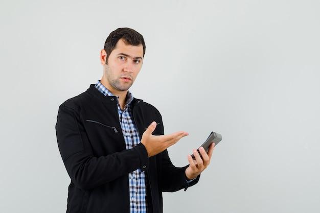 젊은 남자 셔츠, 재킷에 계산기를 보여주는 현명한, 전면보기.