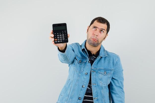 Молодой человек показывает калькулятор в футболке, куртке и смотрит задумчиво, вид спереди.