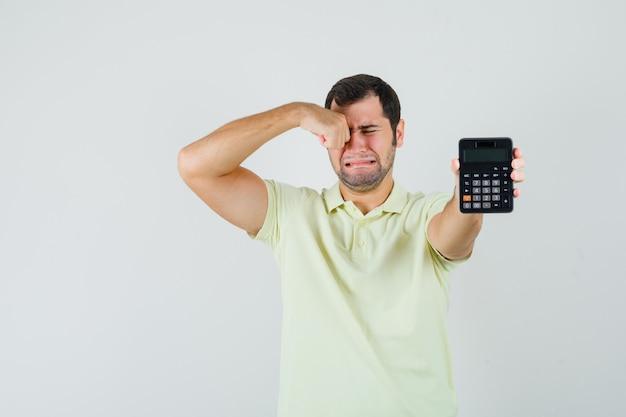 Tシャツ、正面図で泣きながら電卓を示す若い男。