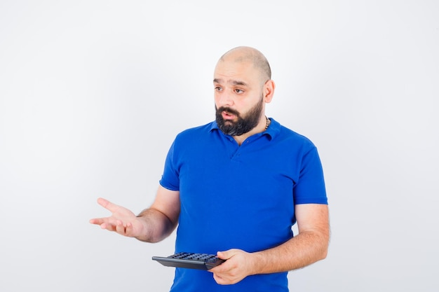 青いシャツで話している間、電卓を見せて、混乱しているように見える若い男、正面図。