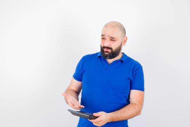青いシャツで話し、集中して見ながら電卓を示す若い男。正面図。