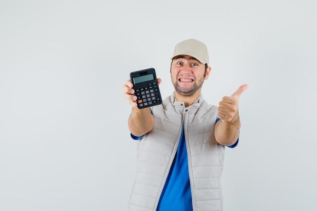 T- 셔츠, 재킷에 엄지 손가락으로 계산기를 표시 하 고 쾌활 한, 전면보기를 찾고 젊은 남자.