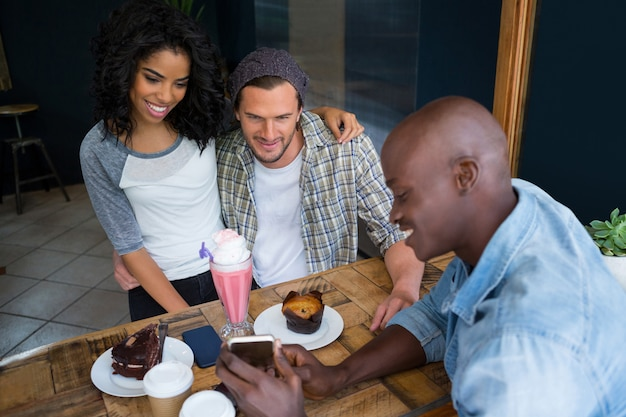 Young man showing cell phone to couple at table in coffee shop