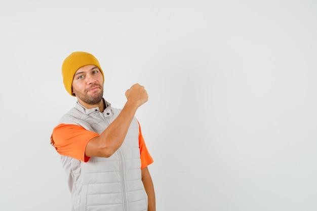 Giovane che mostra il pugno chiuso in t-shirt, giacca, cappello e sembra fiducioso