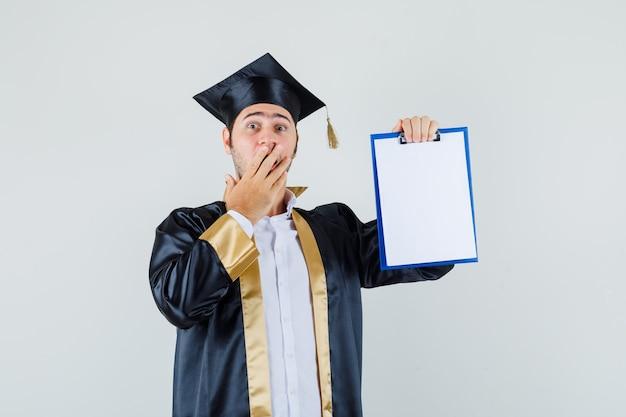Giovane che mostra appunti in uniforme laureato e guardando scioccato. vista frontale.