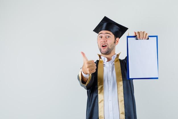 Молодой человек показывая доску сзажимом для бумаги с большим пальцем руки вверх в форме выпускника и смотря рад. передний план.