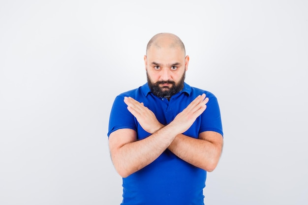 青いシャツで閉じたジェスチャーを示し、焦点を当てた、正面図を探している若い男。