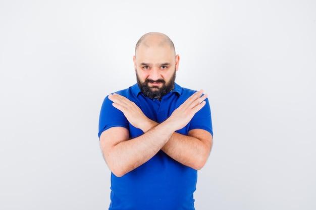 青いシャツを着て閉じたジェスチャーを示し、気が進まない若い男。正面図。