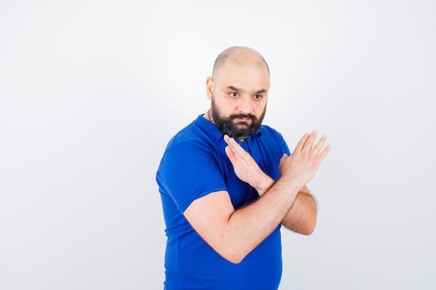 青いシャツで閉じたジェスチャーを示し、真剣に見える若い男。正面図。