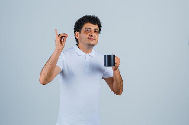 Giovane che mostra gesto delizioso e tiene una tazza di tè in maglietta bianca e jeans e sembra felice, vista frontale.