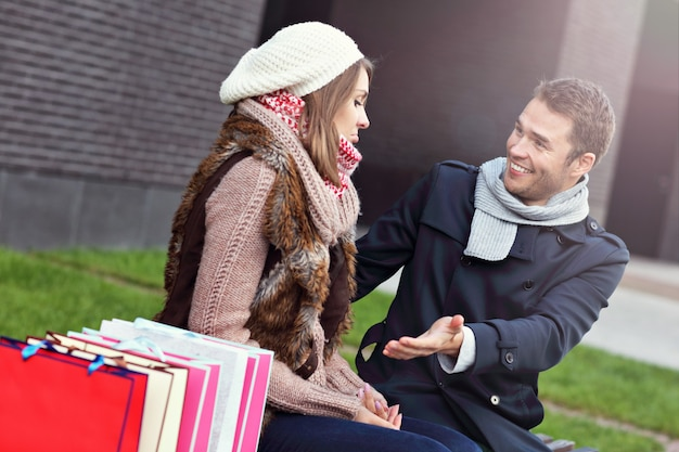 Young man showing disapproval to woman with many shopping bags