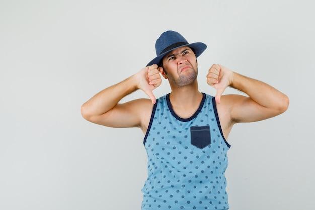 파란색 중항, 모자 및 불만족, 전면보기에서 아래로 두 번 엄지 손가락을 보여주는 젊은 남자.