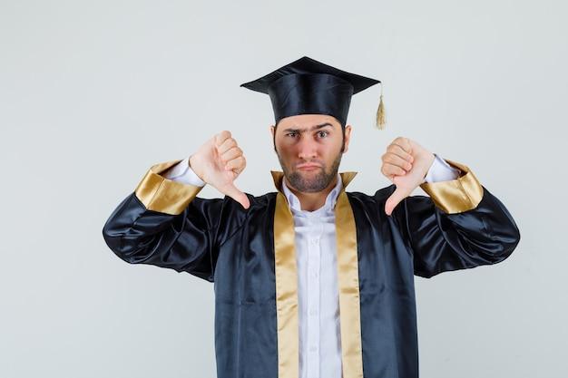 若い男は卒業式の制服を着て二重の親指を下に見せて、真剣に見えます。正面図。