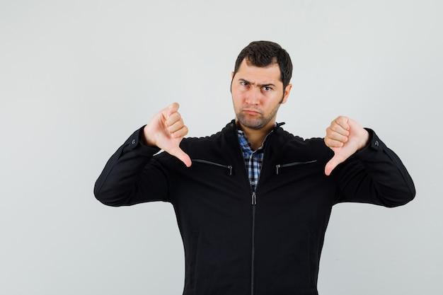 젊은 남자 셔츠, 재킷에 아래로 두 엄지 손가락을 보여주는 심각한 찾고. 전면보기.
