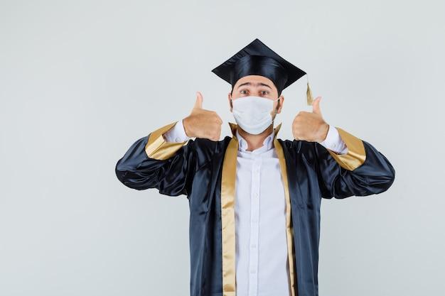 Giovane che mostra i doppi pollici in su in uniforme laureato e che sembra allegro. vista frontale.