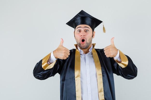 卒業式の制服を着て二重の親指を見せて、至福の正面図を見ている若い男。