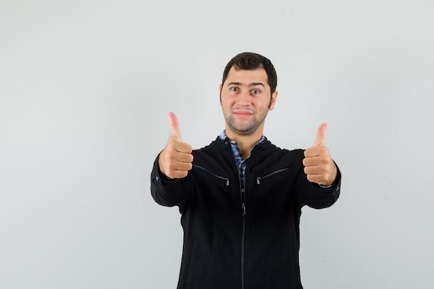 Молодой человек показывает двойные пальцы вверх в рубашке, куртке и выглядит уверенно, вид спереди.
