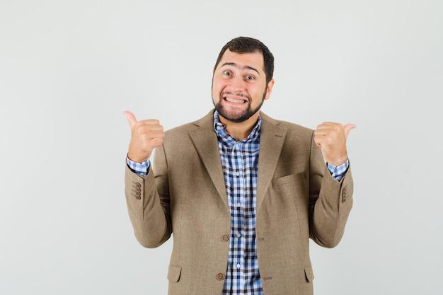 Молодой человек показывает двойные пальцы вверх в рубашке, куртке и выглядит весело.
