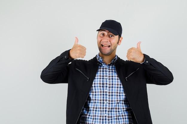 Молодой человек показывает двойные пальцы вверх в рубашке, куртке, кепке и рад, вид спереди.