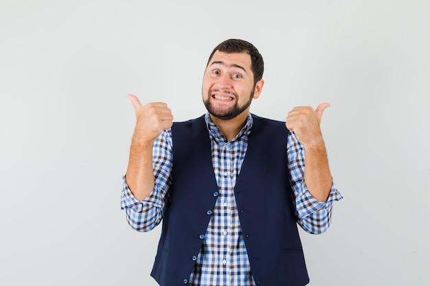 Молодой человек показывает двойные пальцы вверх в рубашке, жилете и выглядит блаженным.