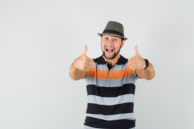 Молодой человек показывает двойные пальцы вверх в футболке, шляпе и выглядит счастливым