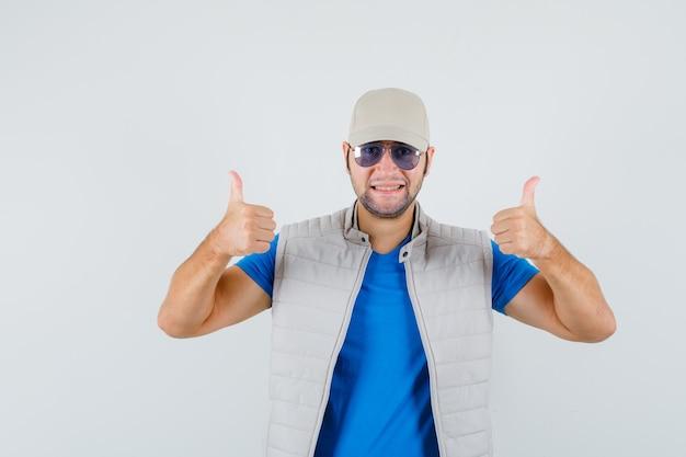 젊은 남자 t- 셔츠, 재킷, 모자에 두 엄지 손가락을 표시 하 고 쾌활 한, 전면보기를 찾고.