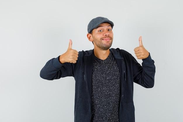 Молодой человек показывает двойные пальцы вверх в футболке, куртке, кепке и выглядит весело