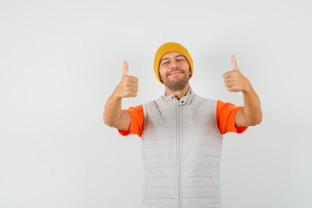 Молодой человек показывает двойные пальцы вверх в футболке, куртке, шляпе и выглядит веселым.