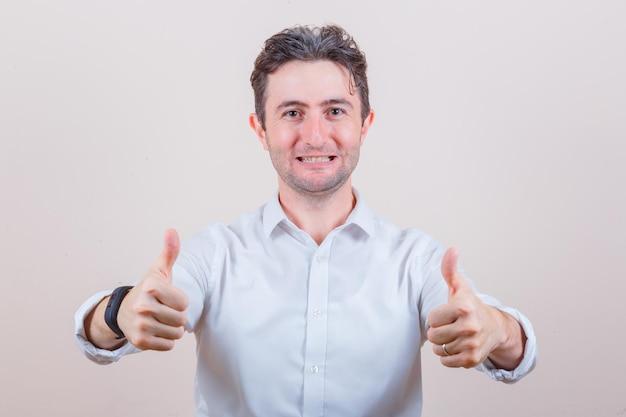 흰 셔츠에 두 엄지 손가락을 보여주는 젊은 남자와 행복을 찾고