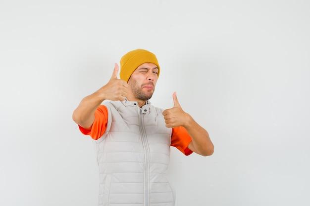 Молодой человек показывает двойные пальцы вверх, подмигивает в футболке, куртке, шляпе