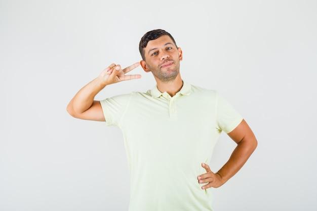 Молодой человек показывает двойной v-образный знак с рукой на талии в футболке и выглядит уверенно