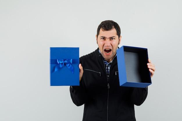 Молодой человек показывает пустую настоящую коробку в рубашке, куртке и выглядит сердитым. передний план.