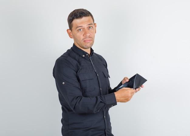 Молодой человек показывает пустой кошелек в черной рубашке и выглядит разочарованным