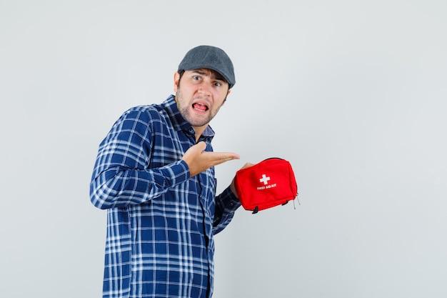 シャツ、キャップで救急箱を見せて、緊張している若い男。正面図。