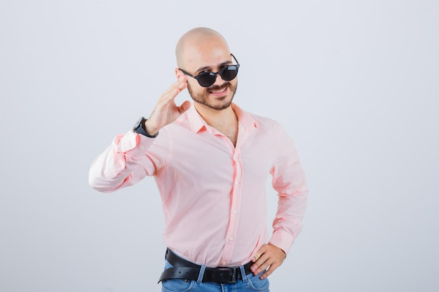 Young man showing greeting gesture in pink shirt,jeans,sunglasses and looking merry , front view.