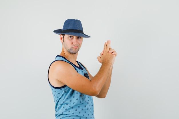 青い一重項、帽子で銃のジェスチャーを示し、自信を持って見える若い男。正面図。