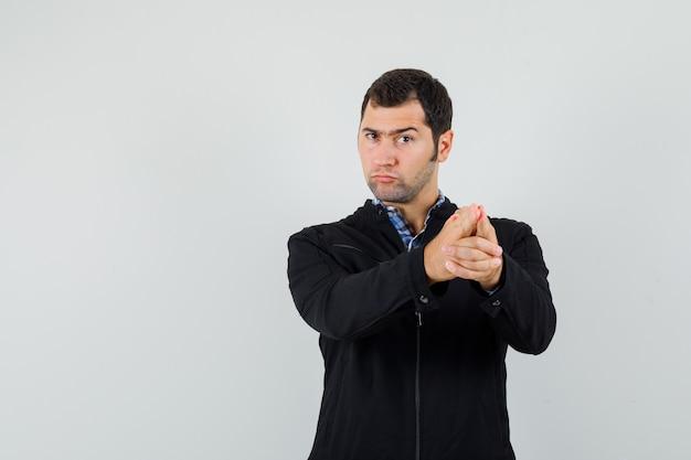 Молодой человек показывает жест пистолета в рубашке, куртке и выглядит сосредоточенным, вид спереди.