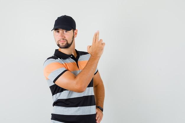 Tシャツ、キャップで銃のジェスチャーを示し、自信を持って見える若い男