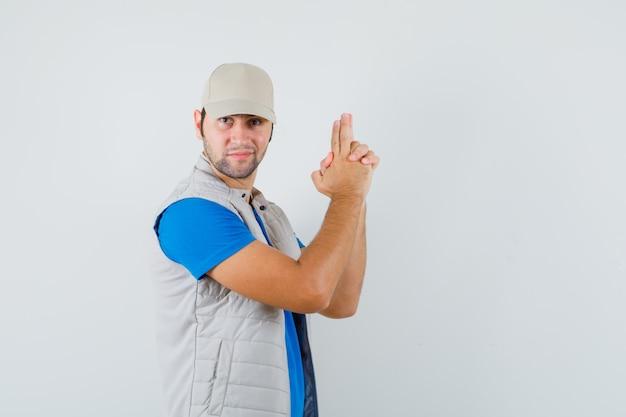 Tシャツ、ジャケット、キャップで銃のジェスチャーを示し、自信を持って、正面図を見て若い男。