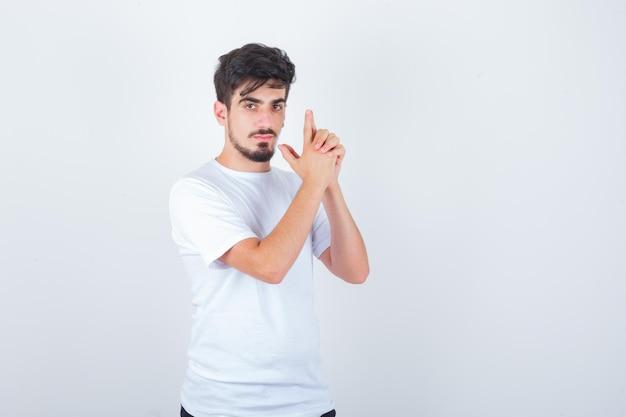 白いtシャツで銃のジェスチャーを示し、自信を持って見える若い男