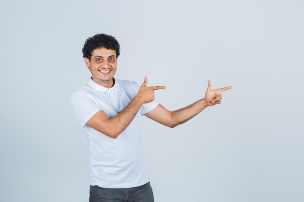 白いtシャツ、ズボンで銃のジェスチャーを示し、自信を持って見える若い男。正面図。