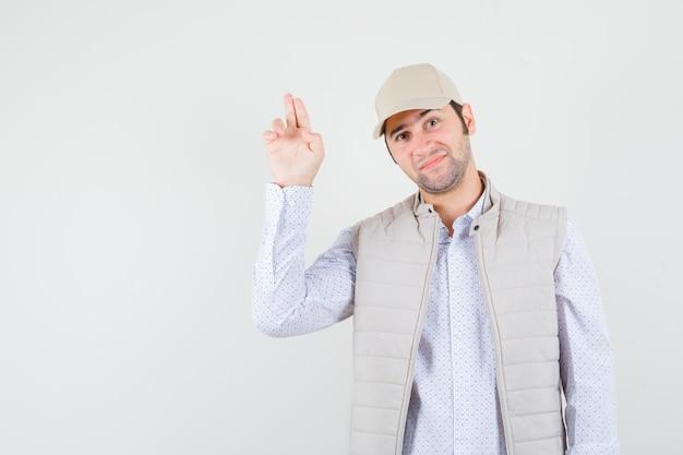 Giovane che mostra il segno della pistola in giacca e berretto beige e che sembra felice, vista frontale.