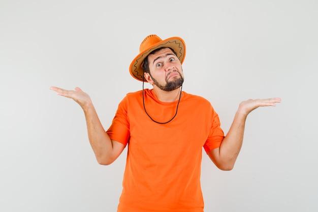 Молодой человек демонстрирует беспомощный жест, пожимая плечами в оранжевой футболке, шляпе и растерянно, вид спереди.
