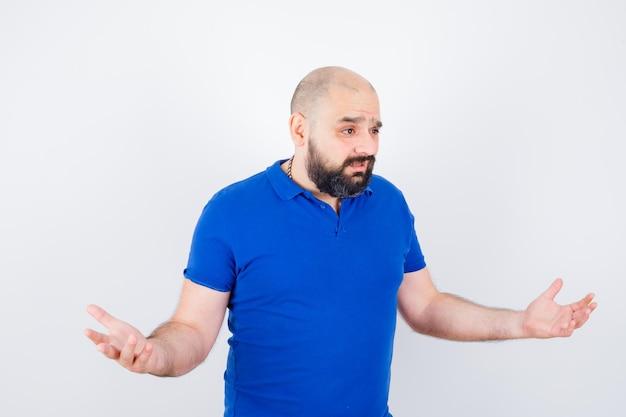 青いシャツの正面図で無力なジェスチャーを示す若い男。