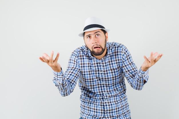 Молодой человек показывает беспомощный жест в клетчатой рубашке, шляпе и выглядит озадаченным