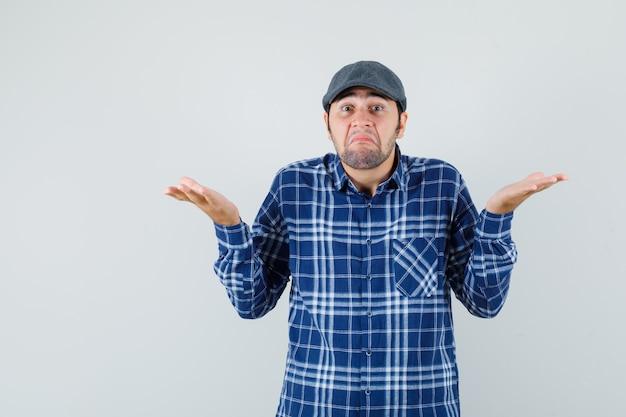 젊은 남자 셔츠, 모자에 무기력 제스처를 보여주는 혼란 찾고. 전면보기.